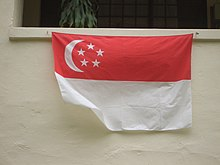 Una casa che visualizza la bandiera nazionale sotto la loro finestra