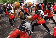 Performers from the group Soh Daiko perform outdoors on various drums in front of an audience.