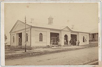 Gympie Court House - Men standing outside one of Gympie's earlier court houses, 1870