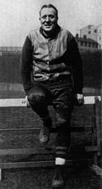 Jock Sutherland sitting on a track and field hurdle.