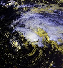 Satellite image of a weak tropical cyclone. The storm has an exposed center situated just south of deep convection. Cirrus clouds extend to the northeast of this area; no land is visible in the image.
