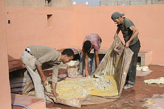 Tadelakt - Mixing plaster powder with water and yellow pigment to make Tadelakt in Riad Dar Rita, Ouarzazate, Morocco.