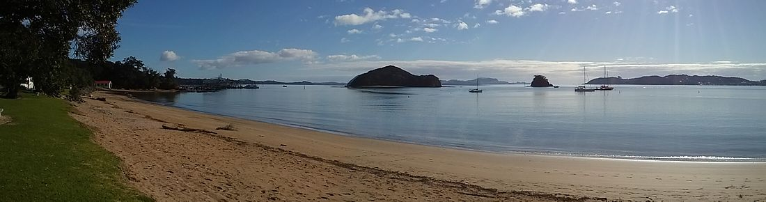Panorama of Taiputuputu Pahi Beach looking north towards Paihia Wharf and Motumarie