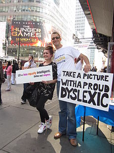 "A girl holding a sign that says ""LD = equally intelligent / Cross out stigma"" poses for a photo in Times Square with a man holding a sign that says ""Take a picture with a proud Dyslexic""."