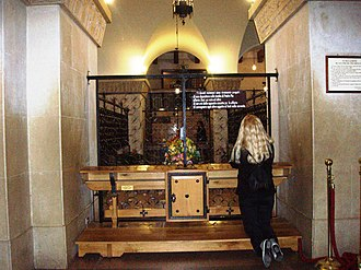 Novena - A woman praying to Padre Pio in San Giovanni Rotondo, Italy, with petitions.