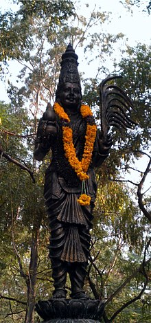 Black outdoor statue with an orange garland