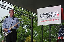 McCotter on stage with a guitar beside a campaign poster