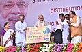 The Prime Minister, Shri Narendra Modi distributing the RuPay cards to beneficiaries, at the Shri Kshetra Dharmasthala Rural Development Project, at Ujire, in Karnataka (1).jpg
