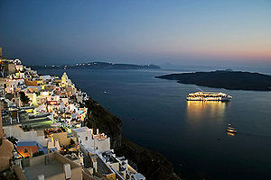 Thira, Santorini at night with cruise ship in ...