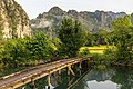 Three-quarter view of a wooden footbridge over a lagoon, trees and mountains in Vang Vieng, Laos.jpg