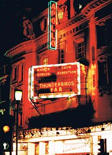 "A neon sign for a stage play at the Apollo Theatre reads ""Andrew Dawson - Gavin Robertson - Thunderbirds FAB - A Forbidden Planet Production"""