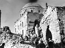 Black & white image showing gaping hole in side of synagogue with soldiers walking atop rubble outside
