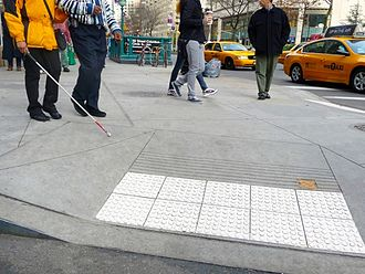 Tactile paving - ADA compliant color contrast detectable warning installation on a high traffic area in New York City.
