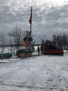 "Mohawk protesters stand by a snowplow covered in Iroquois and Mohawk Warrior flags near a level crossing at Wyman Rd with firewood and a wooden sign that reads ""#RCMP get out""."