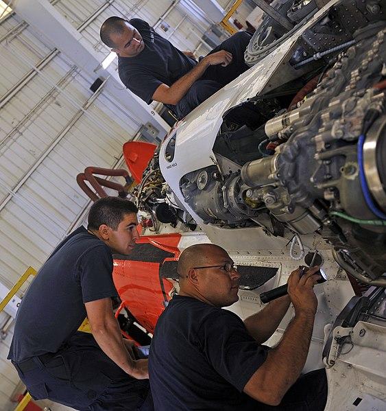 File:U.S. Coast Guard Aviation Maintenance Technician 1st Class Joesoph Villa, bottom right, and Aviation Maintenance Technician 3rd Class Jacob Ylitalo, bottom left, work on an MH-60 Jayhawk helicopter 130801-G-XO423-003.jpg