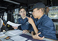 U.S. Navy Quartermaster Seaman Dina Tzegaegbe, right, asks Quartermaster 2nd Class Matthew Cammer a question during training aboard the amphibious dock landing ship USS Pearl Harbor (LSD 52) as part of Pacific 130515-N-SP369-064.jpg