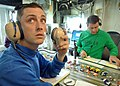US Navy 060522-N-6293B-034 Inside Flight Deck Control, Aviation Boatswain's Mate (Handler) Airman Kenny Lane, left, monitors audio communications and video cameras to update the position of aircraft on the flight deck.jpg
