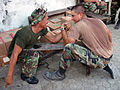 US Navy 060810-N-4689H-003 Utilitiesman 3rd Class Orestes Chavez and an Indonesian Marine take a break from placing tile in an Indonesian elementary school to arm wrestle.jpg