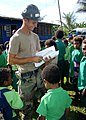 US Navy 080730-N-2941Y-002 Steelworker 3rd Class Michael Featherston hands out coloring books, crayons and frisbees to children.jpg