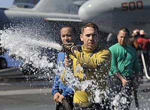 US Navy 111223-N-RG587-286 Aviation Boatswain's Mate (Handling) 3rd Class Sean Pennala hoses down the flight deck of the Nimitz-class aircraft carr.jpg