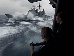 US Navy 111224-N-DR144-349 Hull Technician Fireman Douglas Anderson, left, and Hull Technician Fireman Patrick Zembol watch the Ticonderoga-class g.jpg
