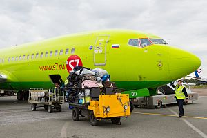 Photograph of luggage being unloaded from an airplane at the airport