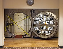 "A large circular metal-lined opening set on a metal bed in a beige wall beneath an ornate silver wall clock reading 10:12. Inside is a space with bars on either side; entry is impaired by two crossed strips of yellow tape with ""caution"" written on it in English and Spanish. To its left is a heavy open door with metal workings behind a glass plate; pieces of paper with individual letters are affixed to it spelling out ""If a bank is too big to fail, it is too big to exist"""
