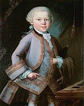 """W. A. Mozart in Hofkleidung aufeinem Ölgemälde von Pietro Antonio Lorenzoni von 1763. Vater Mozart in einem Brief am 19. Oktober 1762: """"Wollen Sie wissen wie des Woferl Kleid aussieht? – Es ist solches vom feinsten Tuch liloa=Farb … Es war für den Prinz Maximilian gemacht ...""""[6] (Quelle: Wikimedia)"""