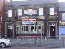 "A large, two-storey, red brick building bears the name ""Old Cannon"" above a large bay window. A banners across the bay window carries the text ""Rent this pub: low ingoings"", and a banner above the same windows says ""property good condition ready to open"" and ""Call now""."