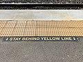'Stay behind yellow line' sign at railway platforms in Queensland, Australia.jpg