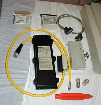 "Ethernet - Older Ethernet equipment.  Clockwise from top-left: An Ethernet transceiver with an in-line 10BASE2 adapter, a similar model transceiver with a 10BASE5 adapter, an AUI cable, a different style of transceiver with 10BASE2 BNC T-connector, two 10BASE5 end fittings (N connectors), an orange ""vampire tap"" installation tool (which includes a specialized drill bit at one end and a socket wrench at the other), and an early model 10BASE5 transceiver (h4000) manufactured by DEC.  The short length of yellow 10BASE5 cable has one end fitted with a N connector and the other end prepared to have a N connector shell installed; the half-black, half-grey rectangular object through which the cable passes is an installed vampire tap."