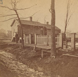 DeKoven Street (Chicago) - The cottage of Catherine and Patrick O'Leary, 137 (now 558) W. DeKoven St. As this view suggests, the neighborhood was congested with mean wooden buildings and a variety of industry, a condition which helped to spread the fire of 1871 as rapidly as it did. A strong wind blowing towards the northeast spared the O'Leary cottage and the buildings seen here to its west. From a stereoptican view by A.H. Abbott, Photographer, whose studio at 976 (now 2201) N. Clark Street was consumed by the flames.