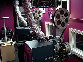 Projectionist - Two projectors installed in a changeover configuration.  The machine in the background will show the first reel, at the end of which the projectionist will 'change over' to reel 2, which is threaded on the projector in the foreground.  If the procedure is performed correctly, the audience will be unaware that it has happened.