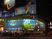 Outside of large, brightly lit store at night in New York City, surrounded by advertisements