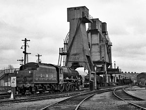 Carnforth MPD - Preserved LMS Jubilee Class No.5690 ''Leander'' moves towards the ash tower with the giant cast-concrete coal stage beyond at Carnforth MPD, built during the 1944 reconstruction of the shed