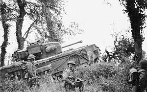 7th Royal Tank Regiment - A Churchill tank of the 7th Royal Tank Regiment supporting infantry of the 8th Battalion, Royal Scots, part of 44th Brigade of 15th (Scottish) Division, during Operation Epsom, 28 June 1944.