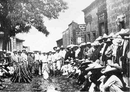Armed Cristeros congregating in the streets of Mexico. The Cristero War was a widespread rebellion against secularist, and anti-Catholic policies of the Mexican government. A la batalla (Cristeros).jpg