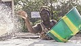 A woman spreads out cassava flour for drying.jpg