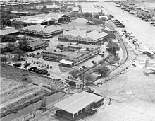 An aerial view of a compound consisting of several buildings, hangars, and small airplanes lining a runway