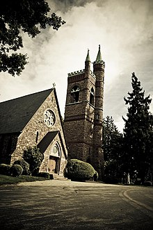 Exterior photograph of All Souls Chapel featuring ornate gothic architecture made of Medina Sandstone and the chapel bell tower.