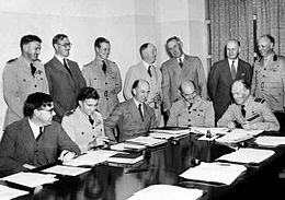 A dozen men behind a large table, half of whom are in military uniform and half in civilian clothes, seven standing and five seated