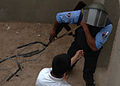 An Iraqi police student arrests a simulated criminal while practicing clearing a building at the police academy in Basra, Iraq, April 20, 2011 110420-A-YD132-158.jpg