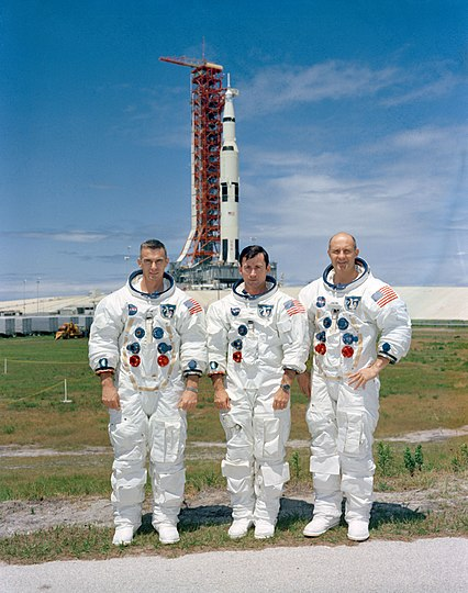 The crew poses with their launch vehicle; left to right, Cernan, Young, Stafford.