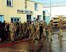 A group of armed soldiers in camouflage uniform with red berets guard a line of enemy soldiers, who stand in front of a large wooden building, which is painted yellow. The road is wet, and the sky is blue.