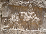 Rock-face relief at Naqsh-e Rustam of Iranian emperor Shapur I (on horseback) capturing Roman emperor Valerian (kneeing) and Philip the Arab (standing)