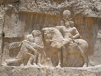 Roman–Persian Wars - Rock-face relief at Naqsh-e Rustam of the Sasanian king Shapur I (on horseback) capturing Roman emperor Valerian (standing) and Philip the Arab (kneeling)