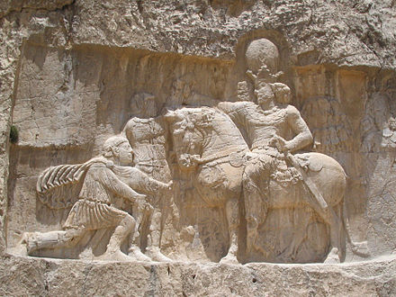 Rock-face relief at Naqsh-e Rustam of Persian emperor Shapur I (on horseback) capturing Roman emperor Valerian (standing) and Philip the Arab (kneeling), suing for peace, following the victory at Edessa. Bas relief nagsh-e-rostam al.jpg