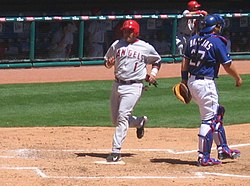 Bengie Molina of the Anaheim Angels (in gray and red) scores a run by touching home plate after rounding all the bases.