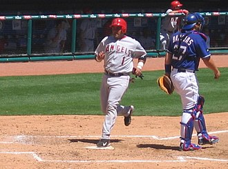 Run (baseball) - Bengie Molina of the Anaheim Angels (in gray and red) scores a run by touching home plate after rounding all the bases.