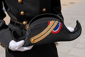Bicorne - The full-dress uniform of École Polytechnique of France comprises black trousers with a red stripe (a skirt for women), a coat with golden buttons and a belt, and a cocked hat (officially called a bicorne).